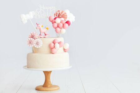 verjaardagstaart voor babymeisje met eenhoorn en ballonnen Stockfoto