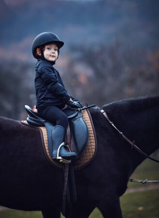 young boy, kid rider stays confidently during horse back ride Reklamní fotografie