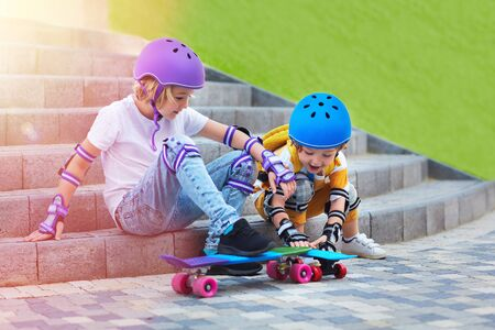 cute young skateboarders, kids in protective equipment are going to skateboard