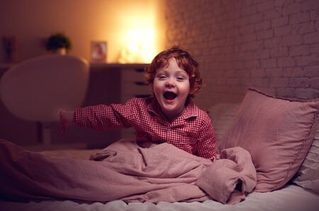 adorable laughing baby boy in bed before going to sleep in the evening