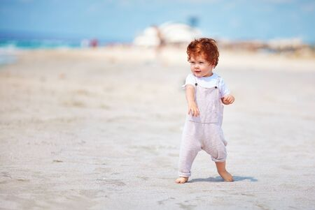 cute toddler baby boy walking on the sandy beach. summer vacation
