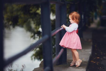 adorable baby girl in fluffy summer dress and sandals on the walk. one and a half year old baby