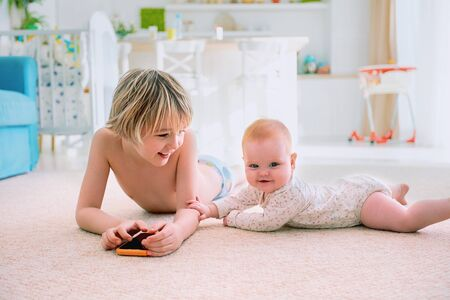 happy infant baby girl playing with elder brother on the carpet at home