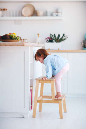 funny infant baby girl climbing a step stool at the cozy kitchen at home 免版税图像 - 151084849