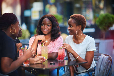 Happy African American Women, friends sitting together at the outdoor restaurant at summer day Stock fotó
