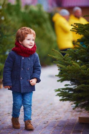 smiling redhead baby boy walking among the trees on christmas fair