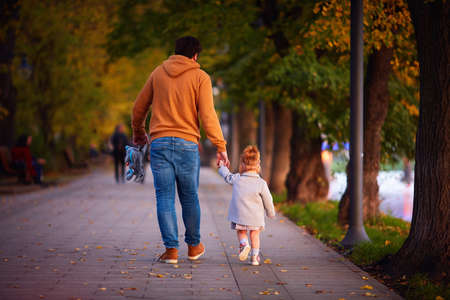 rear view of father with baby girl on the walk on the autumn street