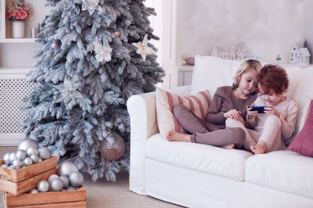 happy kids in pajamas playing on the phone on the sofa during Christmas Holidays 스톡 콘텐츠