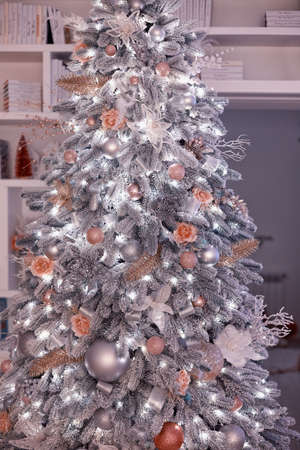 flocked illuminated christmas tree decorated with flowers and ornaments at home