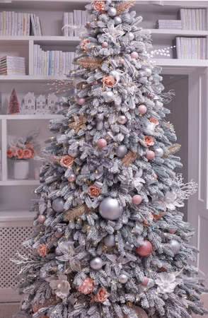flocked decorated christmas tree in front of the book shelves, cozy home interior 스톡 콘텐츠