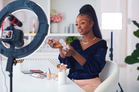 happy young african american woman streaming a beauty vlog from home, online content creator applying a perfume fragrance