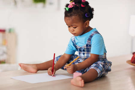 cute toddler baby girl drawing with pencils using both hands