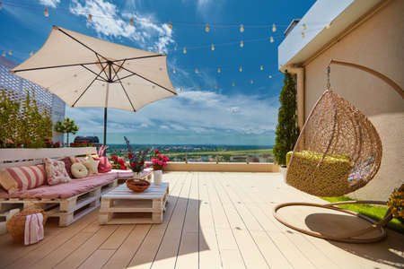 a cozy rooftop patio with wooden pallet furniture and hanging swing chair at sunny summer day Stock fotó