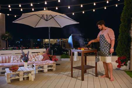 a man grilling barbecue on rooftop patio, enjoys warm summer night at home courtyard