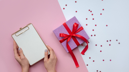 Flat lay . Woman's hands paper. To-do list. Christmas ideas, notes, goals or plan writing concept. Winter holidays. Merry christmas happy new year. Stock Photo