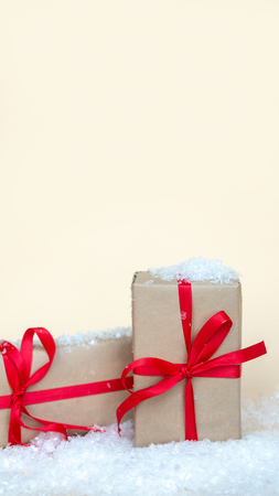 Christmas gift boxes in snow. Gifts with red ribbon. Christmas holiday background. Copy space.