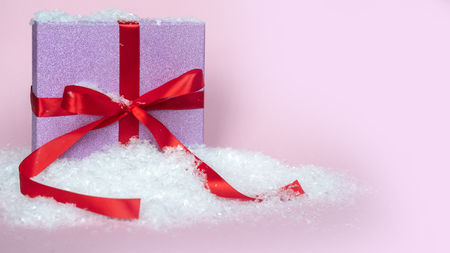 Christmas composition. Pink gift box with red ribbon in snow. Pink background. Stock Photo