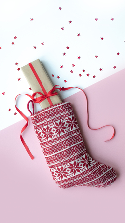 Red christmas sock with gifts on a light background. Christmas background with copyspace. Stock Photo