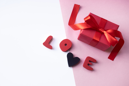 Valentines Day background. Love text with present on white and pink background