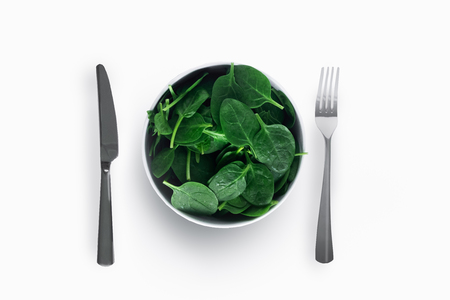 Spinach on white plate with knife and fork on white background.  Healthy eating concept. Banco de Imagens