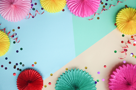 Different paper flowers and confetti on color table top view. Festive or party background. Flat lay style. Copy space for text. Birthday greeting card.