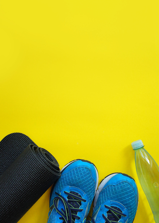 Fitness, healthy and active lifestyles Concept, sport shoes, bottle of waters, mat on yellow background. copy space for text 版權商用圖片