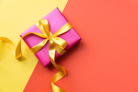 Colorful background with pink gift box. Copy space