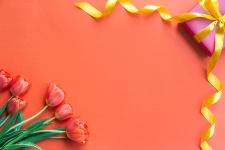 Holidays concept. Beautiful tulips and gift box on orange background. Copy space