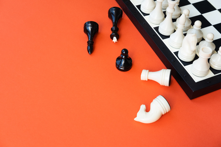 Chess game concept. Chess board with figures on orange    background top view copy space 免版税图像