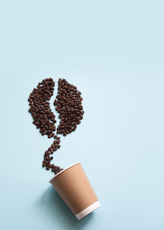 Big coffee bean shape made of coffee beans and paper cup.