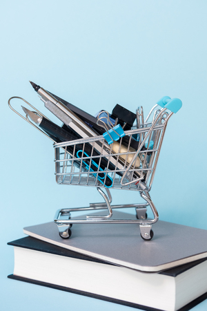 Trolley with different supplies with books on blue background. Education, Back to School, Shopping.