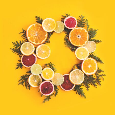 Juicy flat lay with slices of orange, lemon, lime and herbs. Happy yellow summer background, citruses, vitamins concept. Top view, place for text, template for banner, poster.