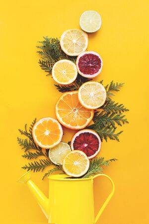 Juicy flat lay with slices of orange, lemon, lime flying out of a watering can. Vitamin vitality concept. Happy yellow summer background, citruses, vitamins concept.