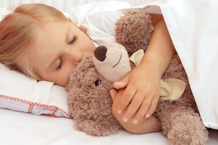 teddies: Adorable little girl sleeping in bed with her teddy bear