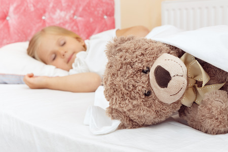 teddy: Adorable little girl sleeping in bed with her teddy bear