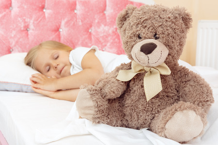 Adorable little girl sleeping in bed with her teddy bear