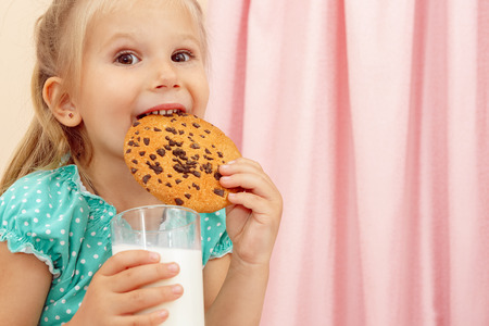 Cheerful little girl with chocolate chip cookies and milk