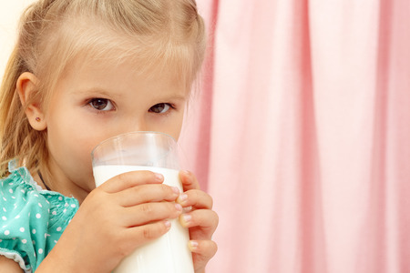 funny glasses: Cheerful little girl with glass of milk Stock Photo