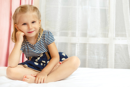 Adorable little girl sitting on the bed Reklamní fotografie