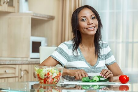 Beautiful woman slicing cucumber for salad in modern kitchen. Stock Photo