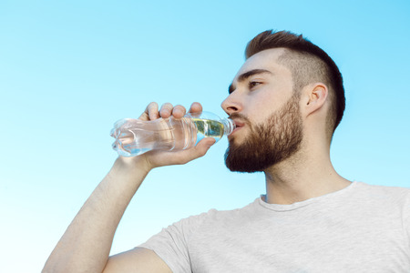 man drinking water: Young man drinking water, hot day Stock Photo