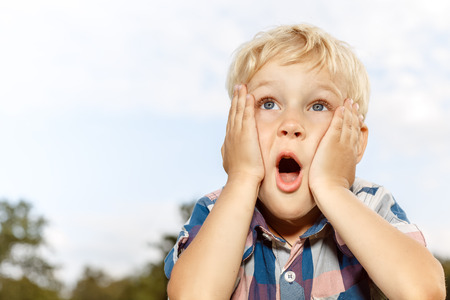 Child expressing surprise with hands on his face
