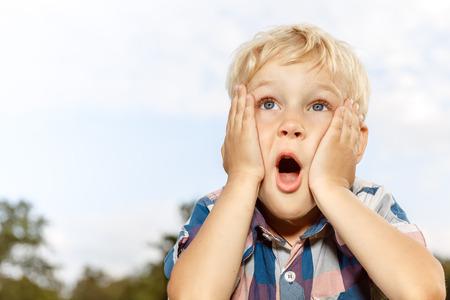 surprised: Niño que expresa sorpresa con las manos en la cara