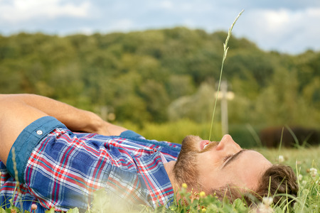 Handsome man lying on the grass in park