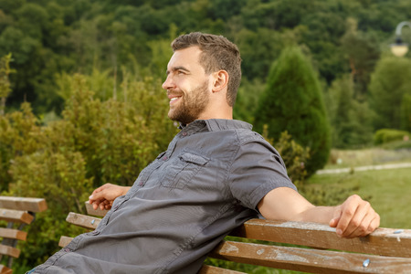 male profile: Man sits on the bench and relax in public park