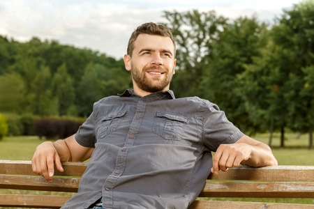 shirt: Man sits on the bench and relax in public park