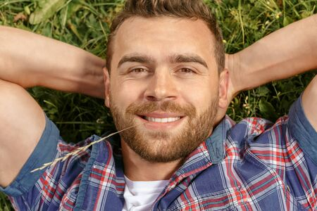 smile close up: Handsome man lying on the grass in park