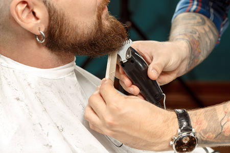 barber chair: Handsome man getting his beard shaved in a barber shop