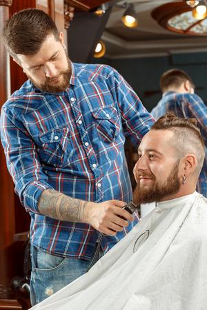barber shop: Knappe mens die zijn baard geschoren in een kapperszaak