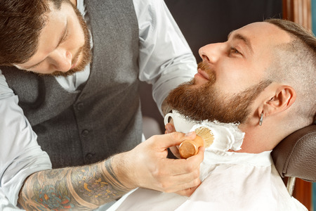barber: Handsome man getting his beard shaved in a barber shop